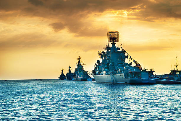 military navy ships in a sea bay - navy stock photos and pictures