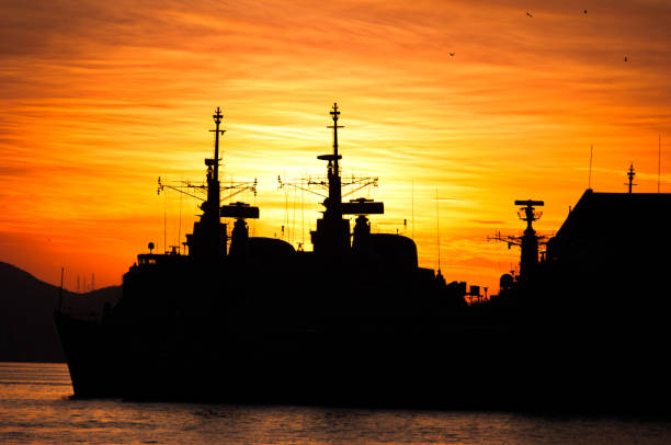 Military Navy Ships Silhouettes by Sunset stock photo