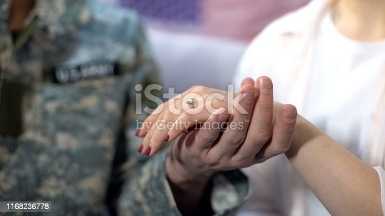 Military officer holding girlfriend hand with engagement ring, proposal close up