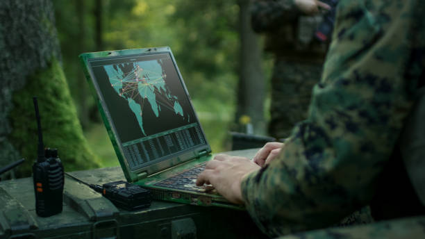 military operation in action, soldiers using military grade laptop targeting enemy with satellite. in the background camouflaged tent on the forest. - armed forces stock photos and pictures