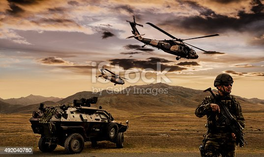 Battlefield with a soldier, armored vehicle and flying helicopters.