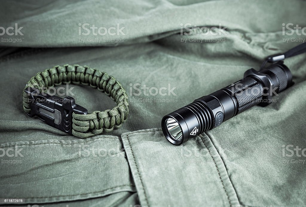 Military paracord bracelet and tactical torch stock photo