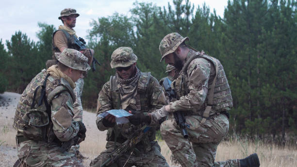 Military people navigating on battlefield Two soldiers sitting in nature and using map and gps tracker for navigation. battlefield stock pictures, royalty-free photos & images