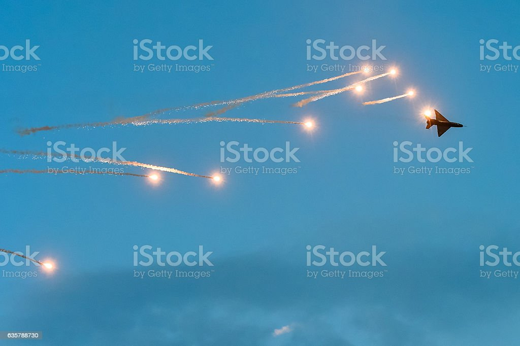 Military plane MIG 21 launching rockets flares at an Airshow stock photo