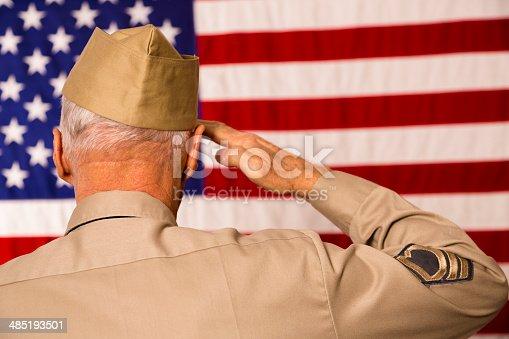 istock Military: Senior veteran in uniform saluting American flag. 485193501