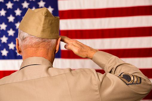 Military: Senior veteran in uniform saluting American flag.