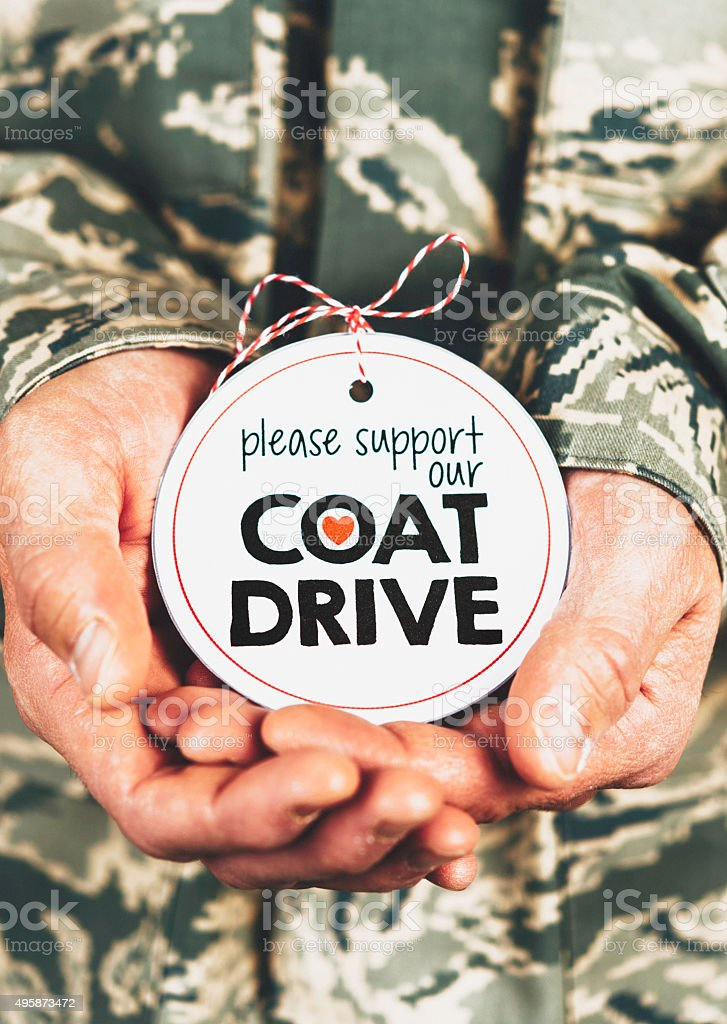 Military service member with coat drive promotion sign stock photo