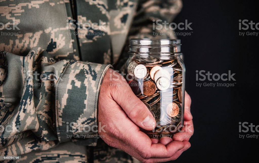 US military serviceman holding jar full of coins stock photo
