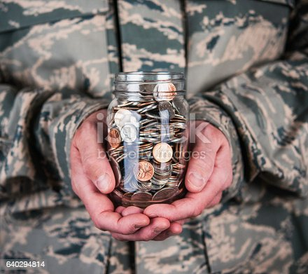 US military serviceman holding jar full of coins