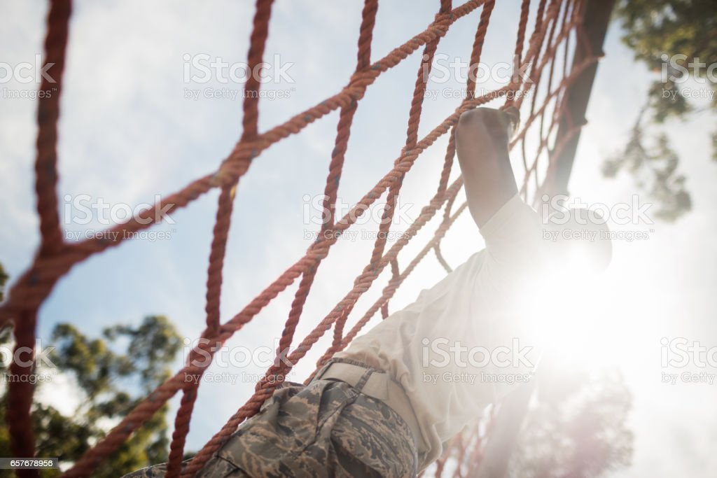 Military soldier climbing rope during obstacle course stock photo