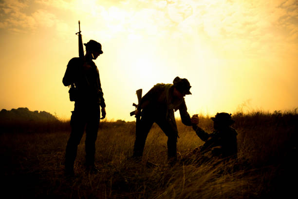 Military soldier holding weapons and help friend stand up. Silhouette of military soldier holding weapons and help friend stand up after get victory of war at sunset. park ranger stock pictures, royalty-free photos & images