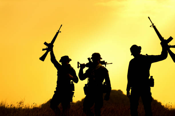 Military soldier holding weapons overhead after get victory. stock photo