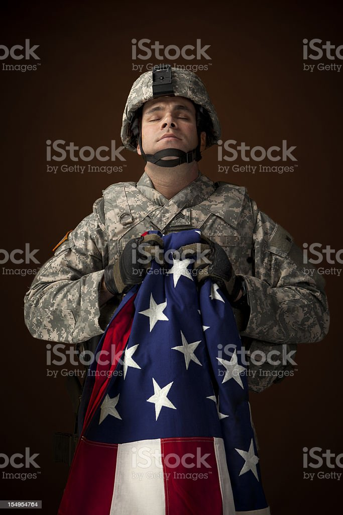 Military Soldier Praying and Hold an American Flag royalty-free stock photo