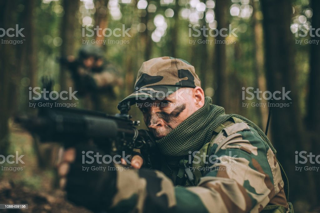 Military soldier shooting a weapon in forest