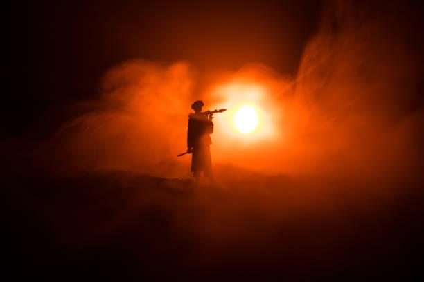 Silueta de soldado militar con Bazooka. Concepto de guerra. Siluetas militares luchando escena en la guerra niebla cielo fondo, soldado silueta apuntando al objetivo en la noche - foto de stock
