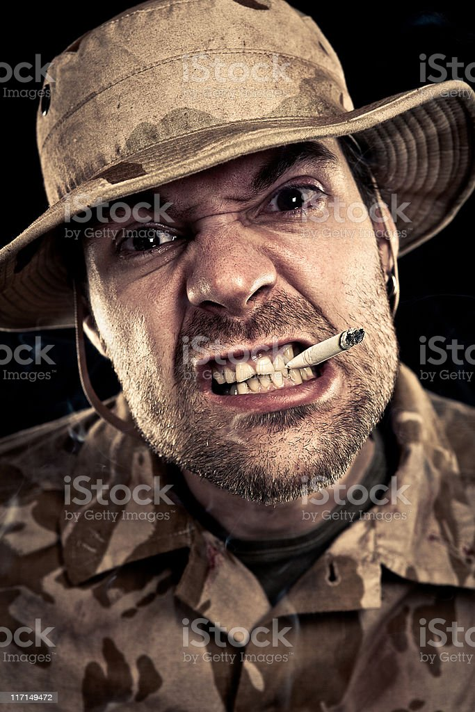 Military Soldier Smoking A Cigarette While Sneering royalty-free stock photo