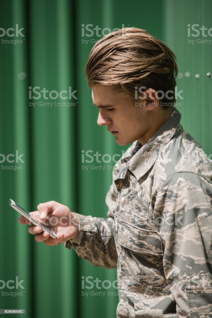 Military soldier using mobile phone stock photo