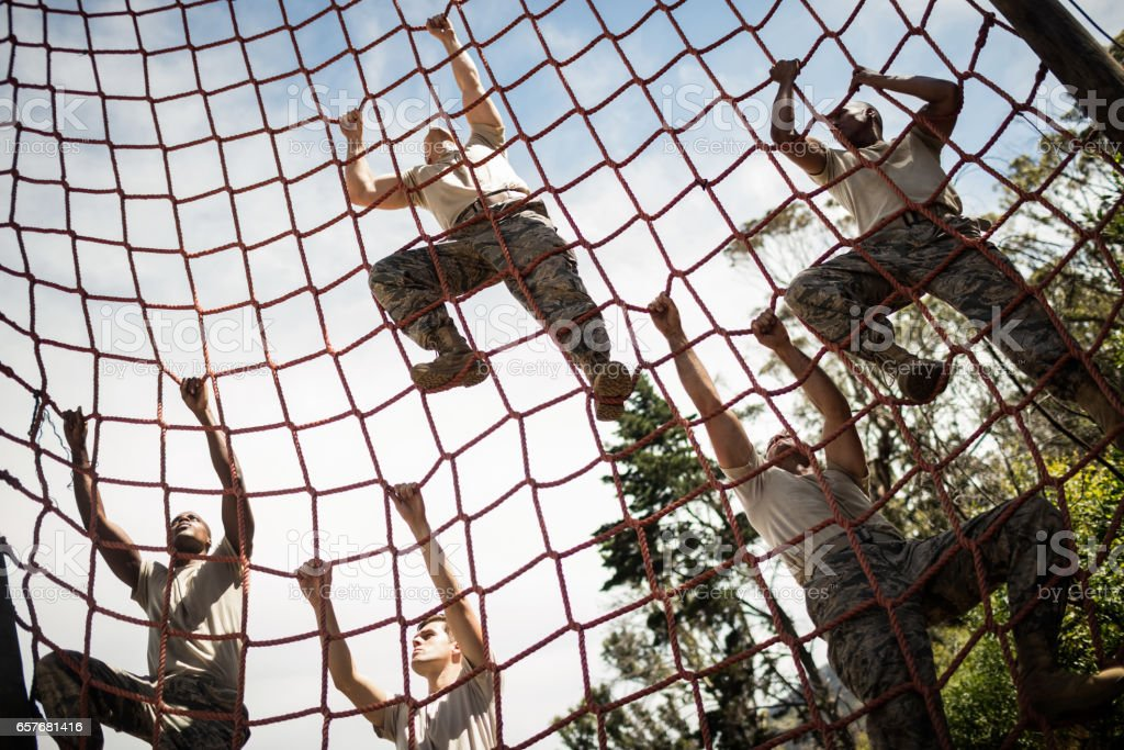 Military soldiers climbing rope during obstacle course stock photo