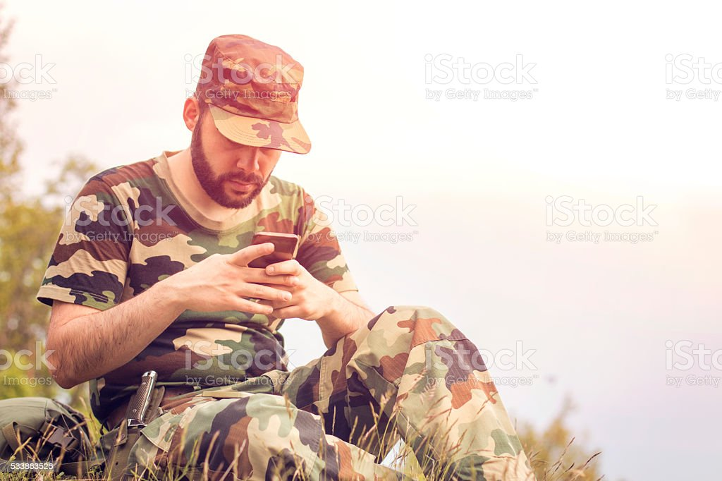 Military solider using digital technology in the field stock photo
