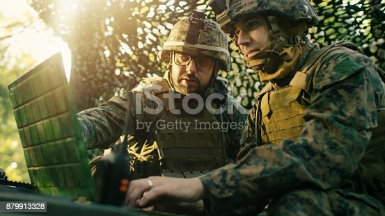istock Military Staging Base, Officer Gives Orders to Chief Engineer, They Use Radio and Army Grade Laptop. They're in Camouflaged Tent in a Forest. They're on Reconnaissance Operation/ Mission. 879913328