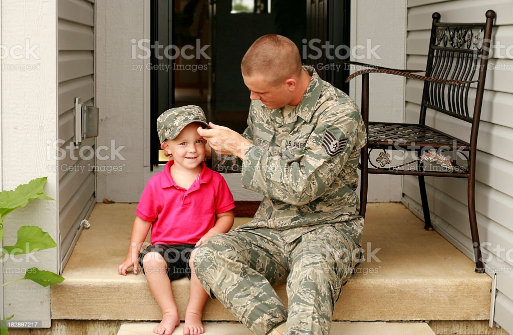 A military styled father letting his son try on his hat stock photo
