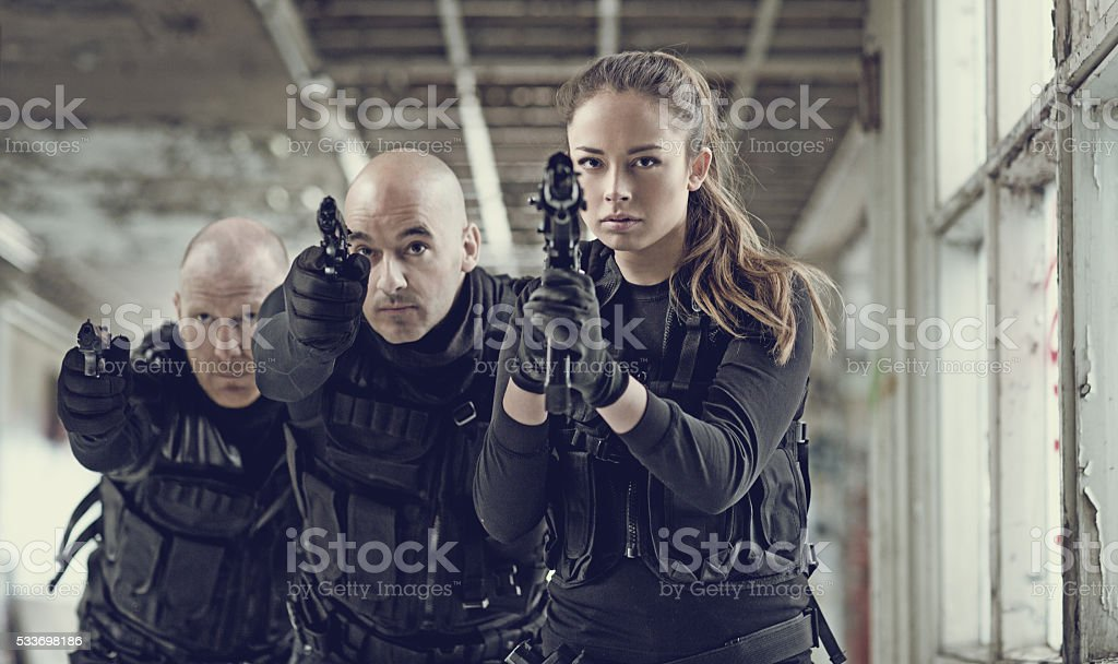 Military swat team members during incursion in abandoned warehouse stock photo