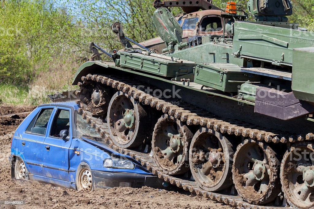 military tank crushes a blue car stock photo