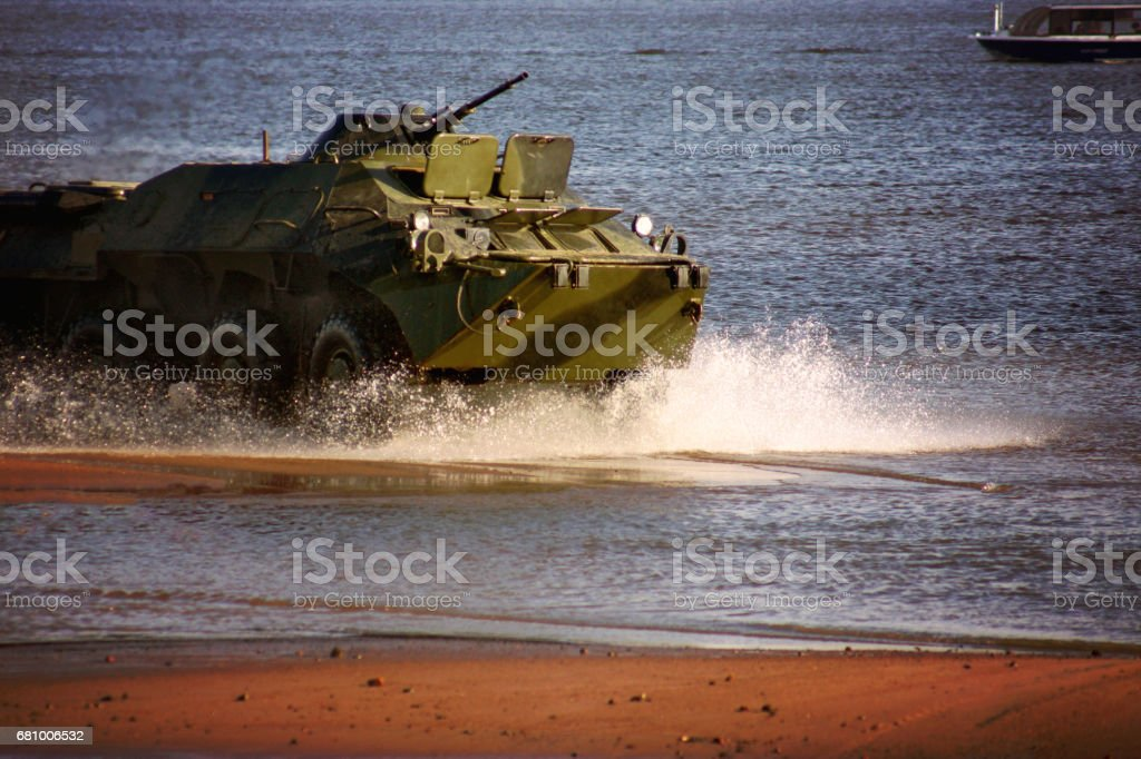 A military tank rides the water at sea, scattering water splashes royalty-free stock photo