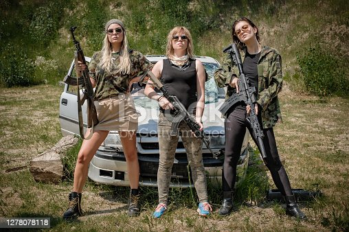 Military team of three attractive female soldier with guns, rifle machine gun and sniper. Woman with weapon. Fashion model style