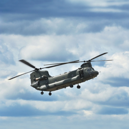 Military transport helicopter Chinook flying under a blue sky with cloud cover.