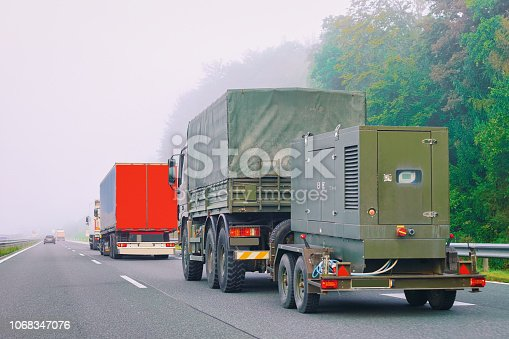 istock Military truck carrying trailer in road in Slovenia 1068347076