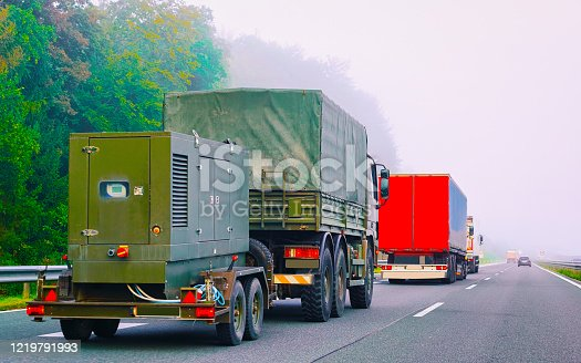 665295184 istock photo Military truck carrying trailer in road in Slovenia 1219791993