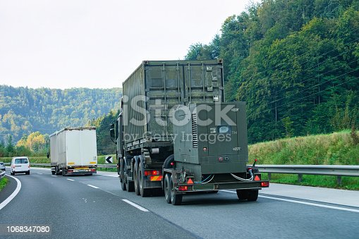 istock Military truck carrying trailer in road of Slovenia 1068347080