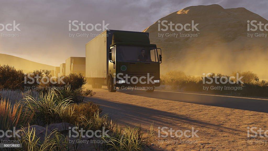 Military trucks on a desert road stock photo