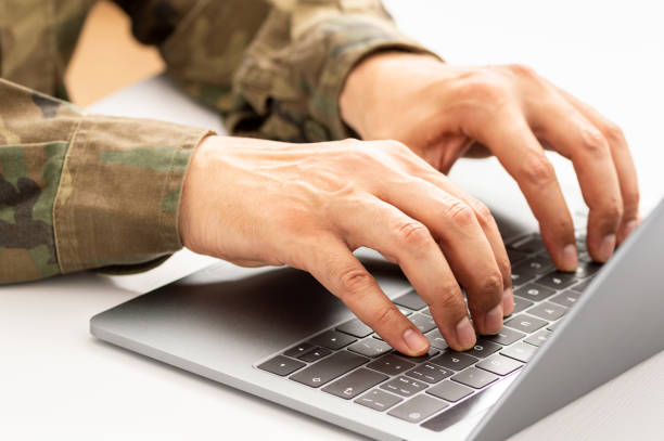 military typing on a laptop stock photo