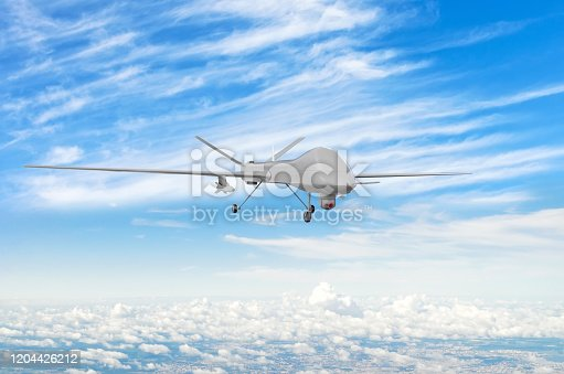 istock Military uav drone flight flies above the clouds. 1204426212