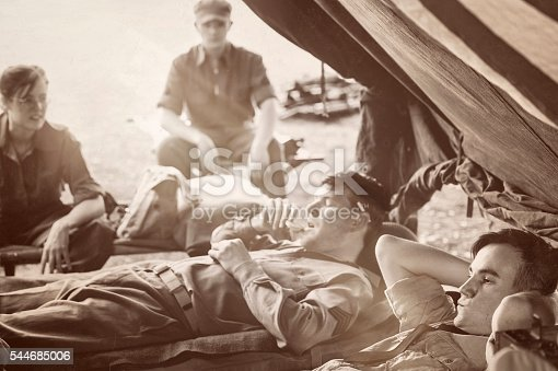 A WWII Military Unit and one worried Naval officer at rest.  Talking, eating, worrying and resting.  Copy Space.