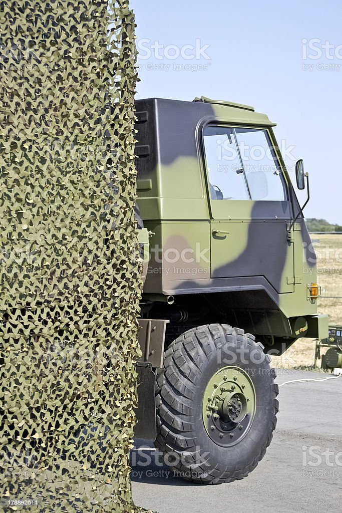 military vehicle hung with camouflage netting royalty-free stock photo