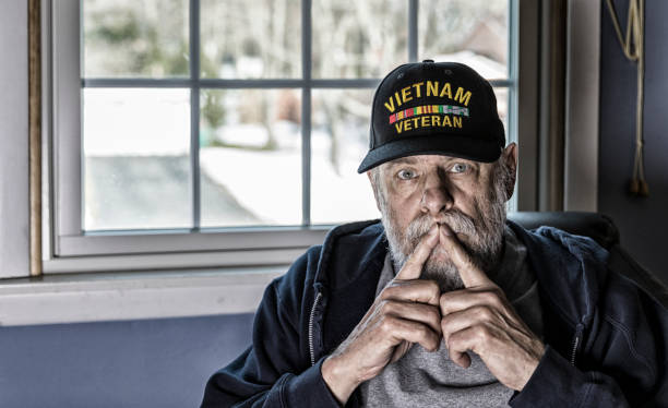 USA Military Vietnam War Veteran With Fingers on Mouth A real person 67 year old United States Navy Vietnam War military veteran is playing with and talking to his pet striped domestic tabby cat who is balanced on a bedroom window sill. post traumatic stress disorder stock pictures, royalty-free photos & images