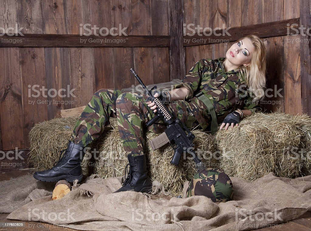 Military woman is lying on straw stock photo
