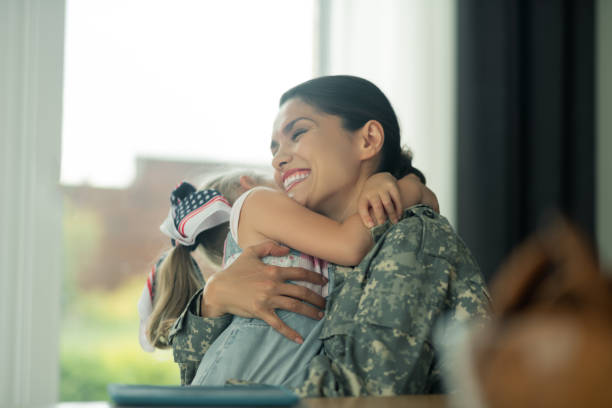 Military woman laughing while hugging her daughter Hugging lovely daughter. Beautiful military woman laughing while hugging her lovely daughter sentimentality stock pictures, royalty-free photos & images