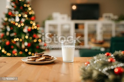 Still life photo of a plate with cookies and a glass of milk that is waiting for Santa Claus. In the back you can see a nice and cosy living room with decorated Christmas tree. No people. Copy space. Daylight.