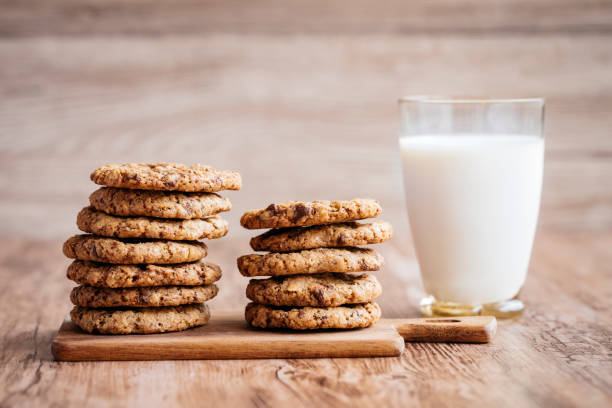 Milk and cookies, homemade with chocolate chips. A glass of milk and some homemade cookies, with melted chocolate chips. The cookies are piled up on a on a little wooden cutting board, lying on a wooden table. The background is wooden as well. sugar cookie stock pictures, royalty-free photos & images