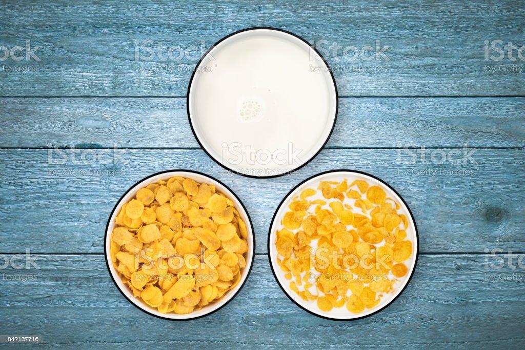 Bols de lait et flocons de maïs sur fond de bois de directement au-dessus - Photo