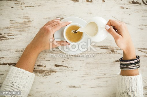 Flat lay of female hands on wooden table holding a cup of tea and pouring milk on it to make a perfect combination before drinking it.