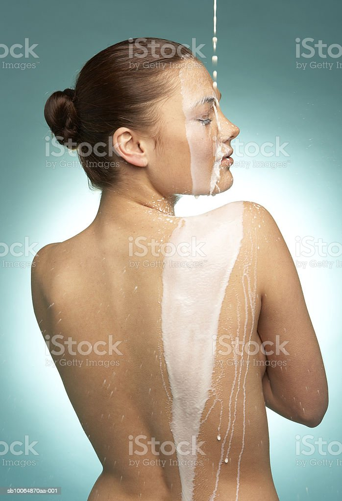 Milk being poured on woman's back, eyes closed foto de stock libre de derechos