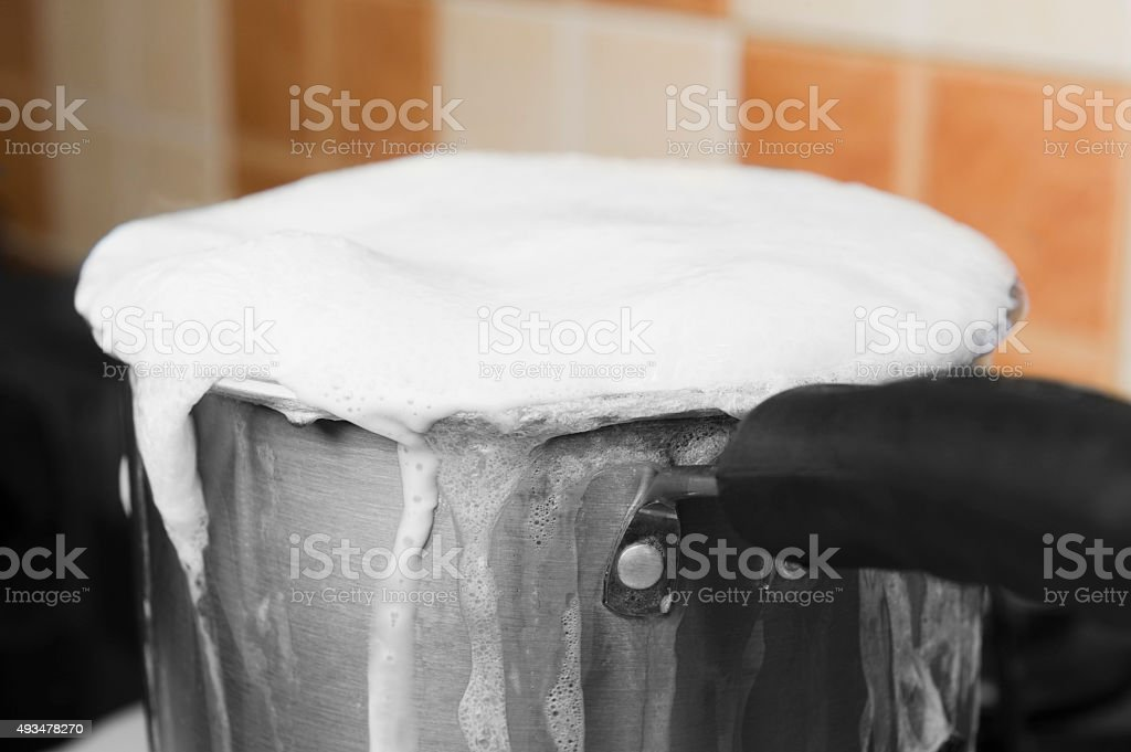 Milk boiling over a pan stock photo