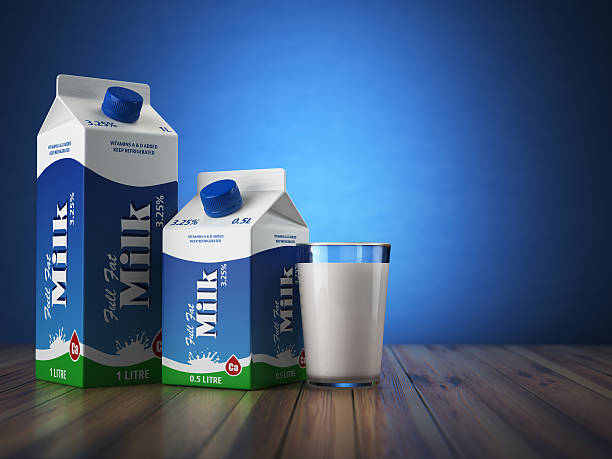 Milk carton packand glass on blue background. - Photo