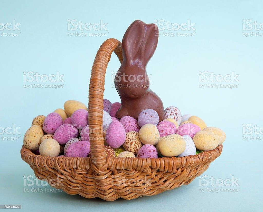 """Coelho Chocolate ao leite em uma cesta com ovos de páscoa """"salpicado"""" foto royalty-free"""