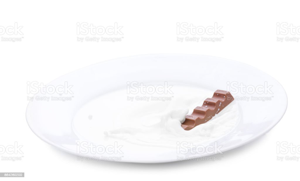 Milk chocolate falling into plate with milk. Milk splash, isolated over white royalty-free stock photo